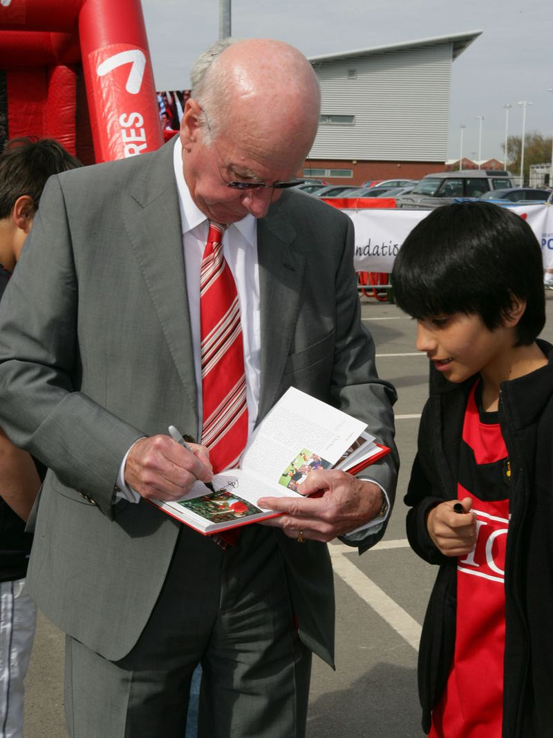 Bobby Charlton signs his autograph for a young fan